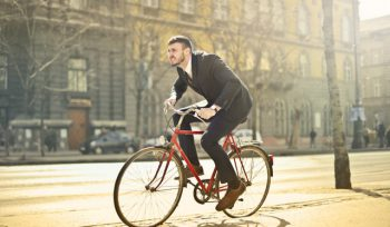 Man in suit riding bike